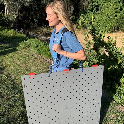 A blonde woman in a blue collared shirt smiles using a shoulder carrying strap attached to the Access Trax gray square mats. There is greenery in the background.