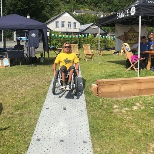 A man in a yellow shirt in a wheelchair uses Beach Trax across grass.