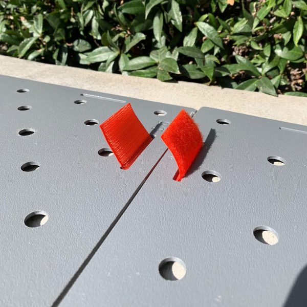 Image shows close up of two Access Trax access mats being connected by an orange Velcro hinge.