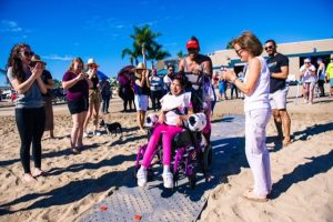 A crowd of people clap and cheer as a mom pushes her daughter smiling in her wheelchair down the Beach Trax path on sand.