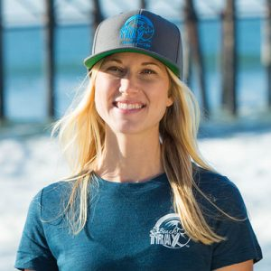 Blonde woman smiling with long hair wearing a Beach Trax logo hat and blue t-shirt.