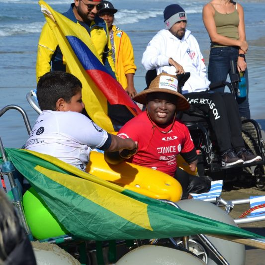 Young male adaptive surfers exit the water using beach wheelchairs and congratulate each other.