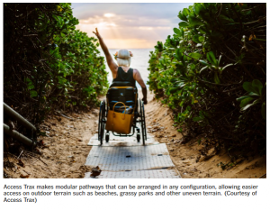 Image of a blonde woman using a wheelchair over a gray pathway towards the beach with green shrubs on either side.