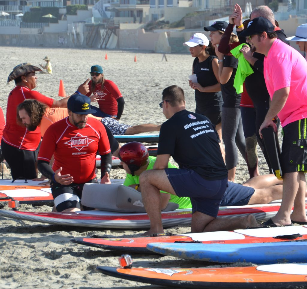 Surf instructors kneel next to a Veteran laying on an adaptive surf board on his stomach to go over surf tips.