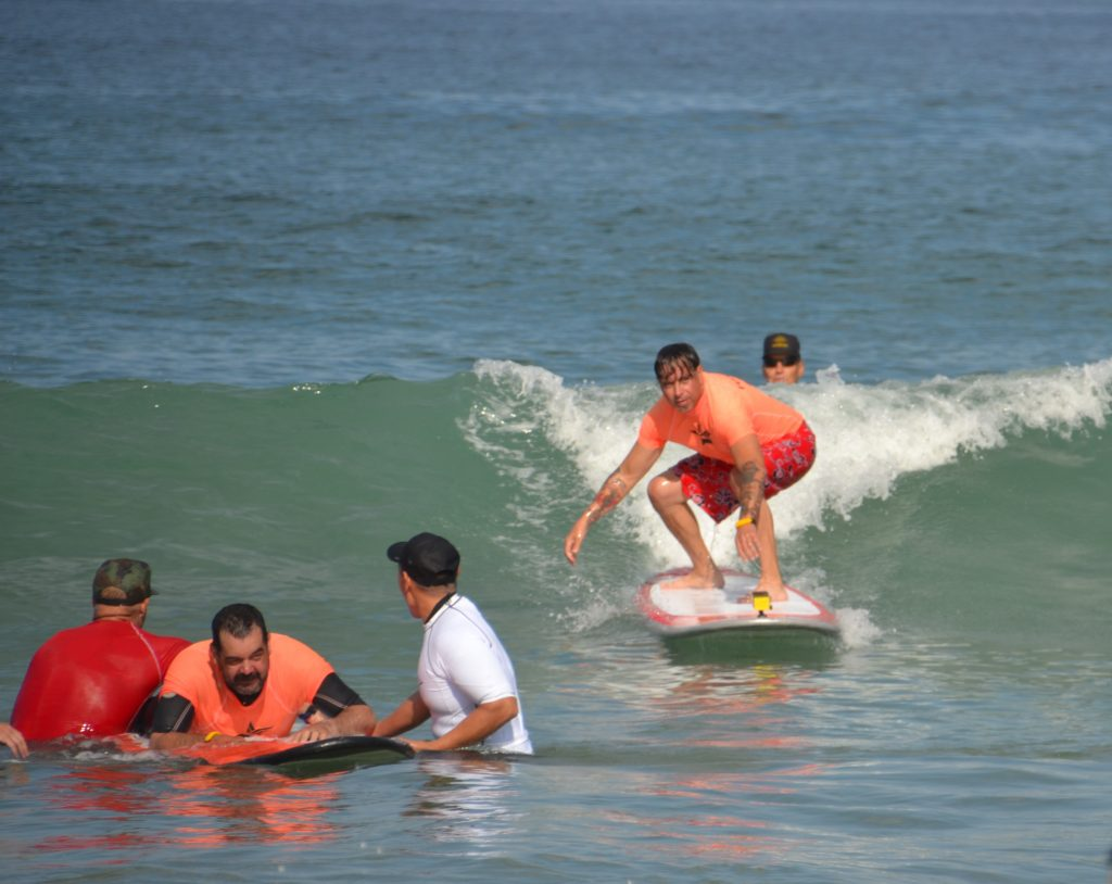 Two male Veterans are attempting to catch a wave on surfboards, one standing crouched low, and the other on his stomach.