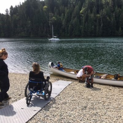 Grey Beach Trax pathway is laid over a rocky lakeshore with a lady in a wheelchair going towards a kayak.