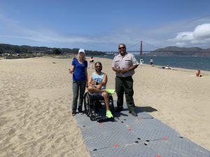 A woman in a blue tshirt with thumbs up and a man wearing a Park Ranger uniform stand next to a man in a blue tank top sitting in his wheelchair on a grey pathway over sand with the Golden Gate Bridge in the background.
