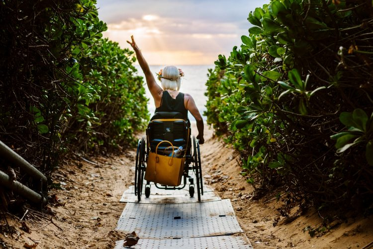 A blonde woman pushes her wheelchair down a grey pathway towards the ocean between large green shrubbery with sunset colors in the clouds above. Her left arm is posed up in the air.