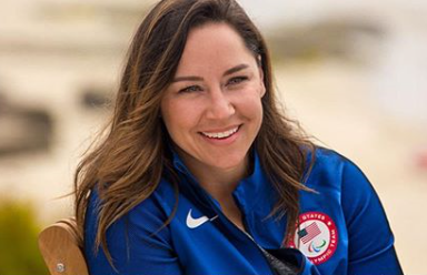 A woman with long brown hair smiles wearing a blue zip up jacket with the USA Paralympic symbol.