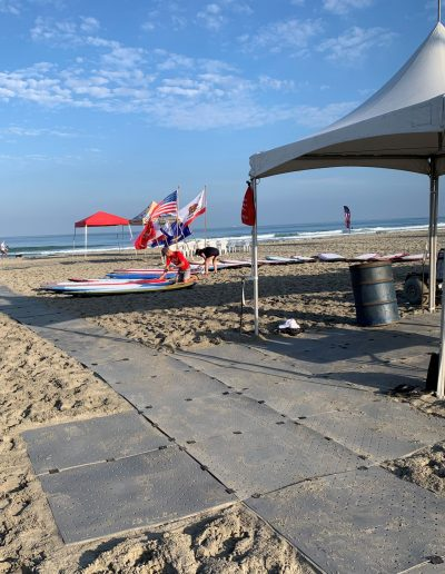 Event set-up at the beach includes water, tents and a portable pathway.