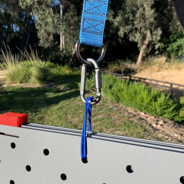 """Image shows blue paracord looped through a 1/2"""" hole lined up across 5 pieces of stacked Access Trax mats. The other end of the paracord is connected to a carabiner which is connected to a metal D ring on the blue carrying strap mechanism. There is grass in the background."""
