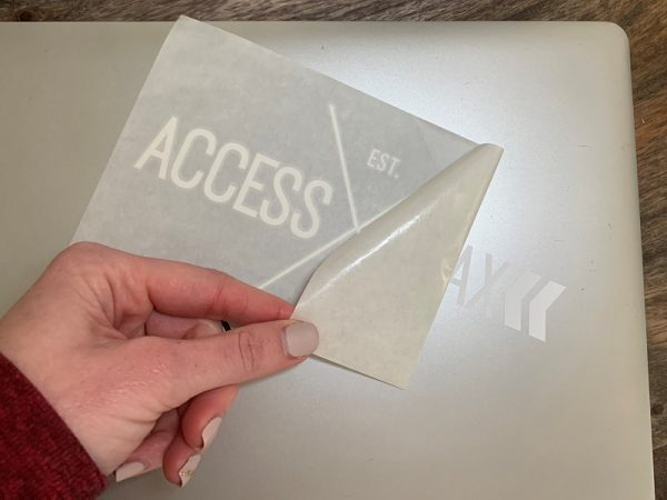Image shows a hand peeling off the clear sticker paper while installing a white vinyl Access Trax logo sticker on a laptop.